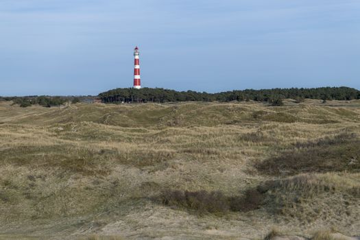 Lighthouse of the island Ameland in northern Netherlands with dunes on the foreground