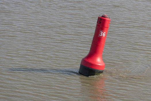 Red buoy as a marker for shipping on the UNESCO protected Wadden Sea in the North of the Netherlands