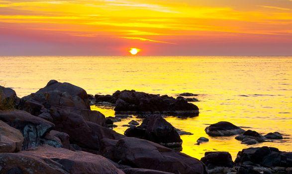 reddish sunrise over the sea with rocky shore