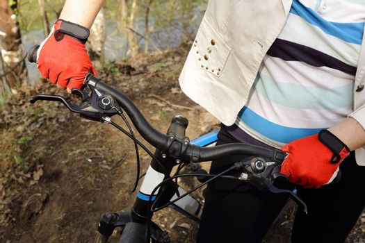 the figure of a woman to the waist. hands holding the wheel of a bicycle. against the background of the forest and the lake.
