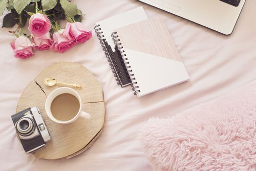 Coffee, old vintage camera in bed on pink sheets. Roses, notebooks and laptop around. Freelance fashion home femininity workspace in flat lay style