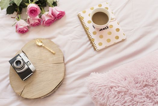 Coffee, old vintage camera in bed on pink sheets. Roses and notebooks around. Freelance fashion home femininity workspace in flat lay style