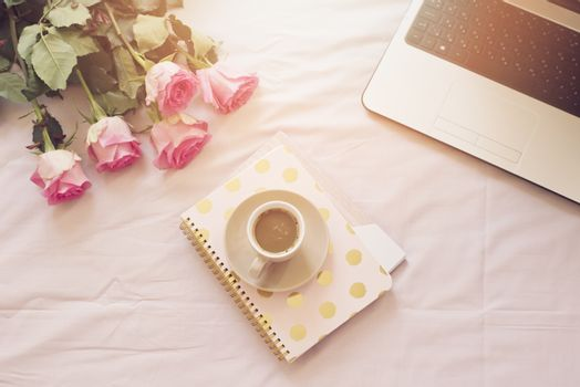 Coffee, old vintage camera in bed on pink sheets. Roses, notebooks and laptop around. Freelance fashion home femininity workspace