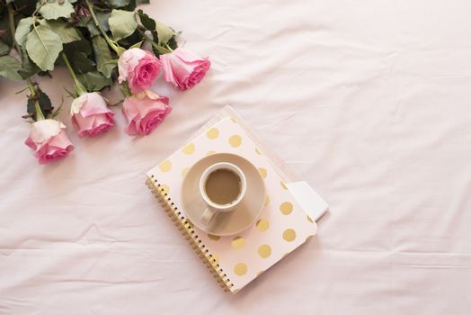 Coffee in bed on pink sheets. Roses, notebooks around. Freelance fashion home femininity workspace