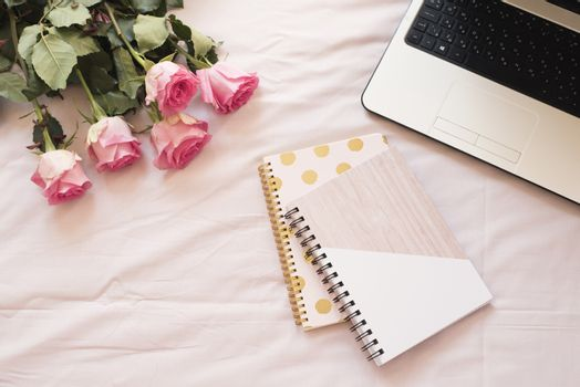 Notebooks, laptop, bouquet of roses in bed on pink sheets. Freelance fashion home femininity workspace in flat lay style.