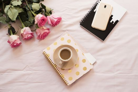 Coffee in bed on pink sheets. Roses, notebooks, gold smartphone around. Freelance fashion home femininity workspace
