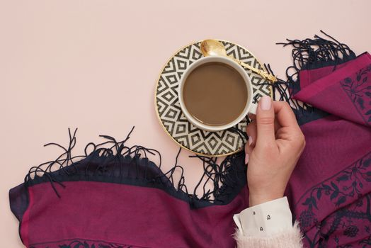 Women hand holding coffee. Latte in a white, black and gold coffee cup. Feminine workplace concept. Freelance fashion comfortable femininity workspace with coffee. Bright pink and purple background