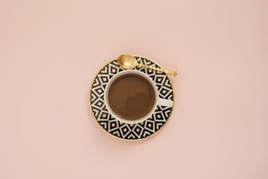 Coffee on a pastel punchy pink background.  Latte in a white, black and gold coffee cup. Feminine workplace concept. Freelance fashion comfortable femininity workspace with coffee