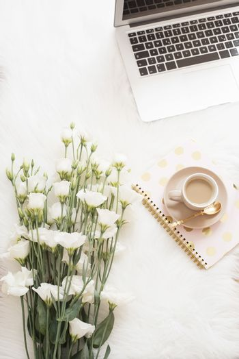 Laptop, coffee, notebook and a large bouquet white flowers on the floor on a white fur carpet. Freelance fashion comfortable femininity home workspace in flat lay style. Top view, pink and gold