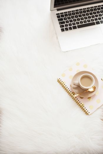 Laptop, coffee and notebook on the floor on a white fur carpet. Freelance fashion comfortable femininity home workspace in flat lay style. Top view, pink and gold. Vertical image, copy space