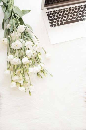 Laptop and a large bouquet white flowers on the floor on a white fur carpet. Freelance fashion comfortable femininity home workspace in flat lay style. Top view, pink and gold. Vertical image