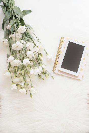 Notebook, tablet and a large bouquet white flowers on the floor on a white fur carpet. Freelance fashion comfortable femininity home workspace in flat lay style. Top view, pink and gold. Vertical image