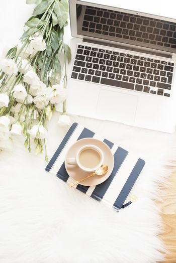 Notebook, laptop, a cup of coffee and a large bouquet white flowers on the floor on a white fur carpet. Freelance fashion comfortable femininity home workspace in flat lay style. Top view, stripe and gold