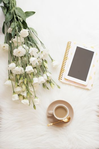 Notebook, tablet, a cup of coffee and a large bouquet white flowers on the floor on a white fur carpet. Freelance fashion comfortable femininity home workspace in flat lay style. Top view, nude and gold