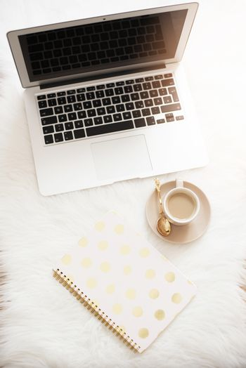 Laptop, coffee and notebook on the floor on a white fur carpet. Freelance fashion comfortable femininity home workspace in flat lay style. Top view, pink and gold. Vertical image