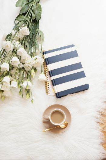 Notebook, tablet, a cup of coffee and a large bouquet white flowers on the floor on a white fur carpet. Freelance fashion comfortable femininity home workspace in flat lay style. Top view, stripe and gold