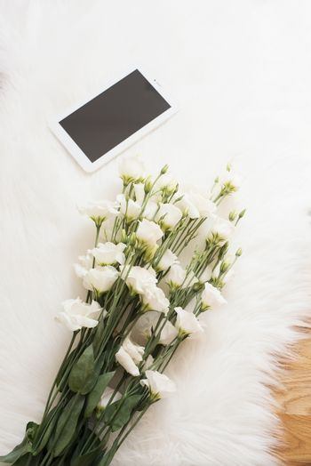 A large bouquet white flowers and tablet on the floor on a white fur carpet. Cozy, fashion comfortable femininity home workplace. Flat lay style. Top view, vertical image