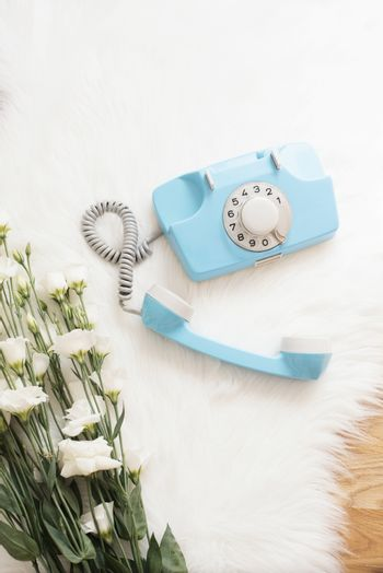 A large bouquet white flowers and blue retro phone on wood floor on a white fur carpet. Cozy, fashion comfortable femininity home. Flat lay style. Top view, vertical image