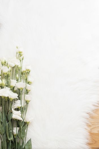 A large bouquet white flowers on wood floor on a white fur carpet. Cozy, fashion comfortable femininity home. Flat lay style. Top view, vertical image