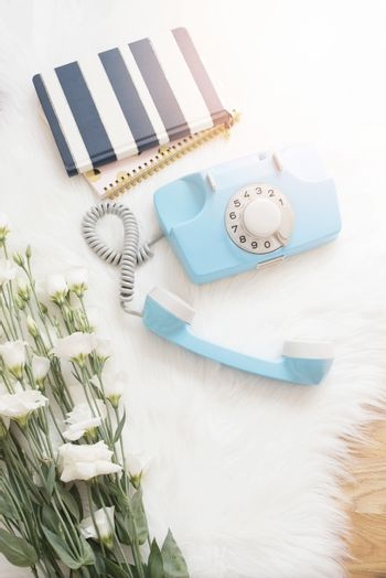 A large bouquet white flowers, notebooks and blue retro phone on wood floor on a white fur carpet. Cozy, fashion comfortable femininity home. Flat lay style. Top view, vertical image