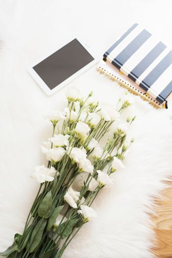 A large bouquet white flowers, notebooks and tablet on the floor on a white fur carpet. Cozy, fashion comfortable femininity home workplace. Flat lay style. Top view, vertical image