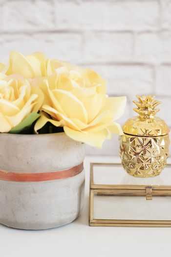 Feminine workplace concept. Freelance fashion comfortable femininity workspace with flowers and golden pineapple on white background. Yellow and gold. Vertical image