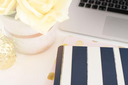 Feminine workplace concept. Freelance fashion comfortable femininity workspace with flowers, stripe notebooks on white background. Bright, yellow and gold. Sun haze, glare