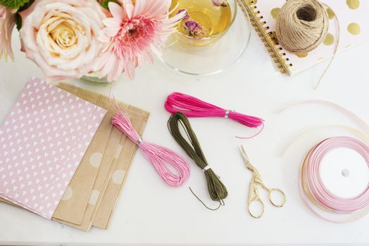 Handmade, craft concept. Materials for making string bracelets and handmade goods packaging - twine, ribbons. Feminine workplace concept. Freelance fashion femininity workspace in flat lay style with flowers, rose tea, notebooks