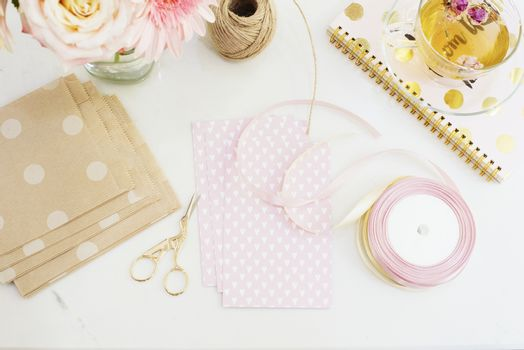 Handmade, craft concept. Handmade goods for packaging - twine, ribbons. Feminine workplace concept. Freelance fashion femininity workspace in flat lay style with flowers, rose tea, notebooks