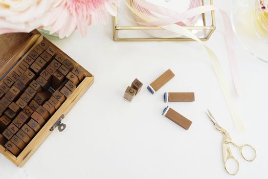 Handmade, craft concept. Wooden rubber stamps, golden scissors, ribbons. Feminine workplace concept. Freelance fashion femininity workspace in flat lay style with flowers, rose tea