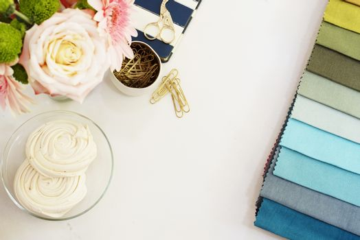 Fabric samples on the table. The designer workplace concept. Freelance fashion comfortable femininity workspace in flat lay style with flowers on white marble background. Top view, bright, pink and gold