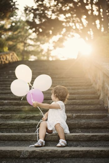 Baby girl standing on stairs and holding balloons. Vintage looking. Sun, sun haze, glare