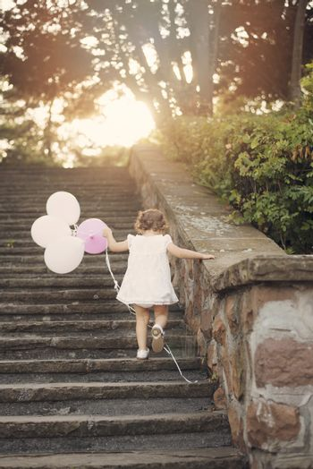 Baby girl on stairs and holding balloons. Vintage looking. Sun, sun haze, glare