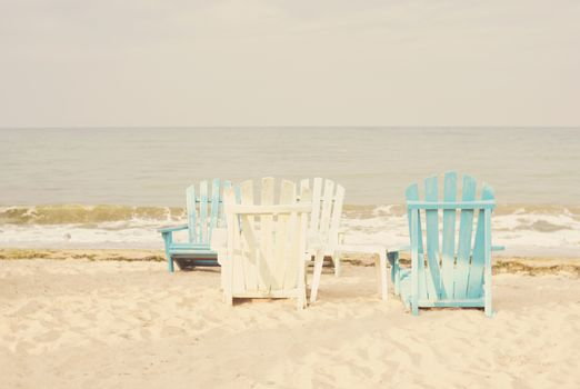White and blue beach chairs on sand seascape and bright sky in summer vacation relax. Vintage filter tinting, sun haze, glare
