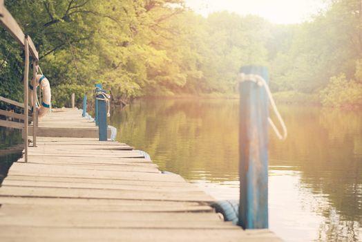 Vintage tone image of old wooden pier in the river, Ropotamo river in Bulgaria. Sun haze, glare