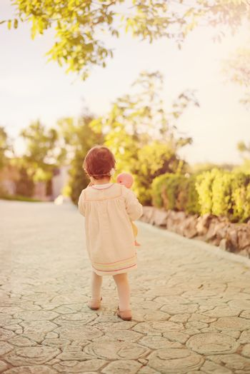 Toddler girl in the back, dressed in a bright dress with a wreath of flowers on his head and holding a doll. Little girl walking down an stone alley in a garden with flowers and trees. Sun, sun haze, glare.