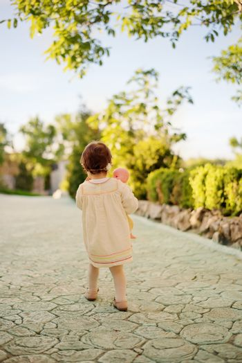 Toddler girl in the back, dressed in a bright dress with a wreath of flowers on his head and holding a doll. Little girl walking down an stone alley in a garden with flowers and trees.
