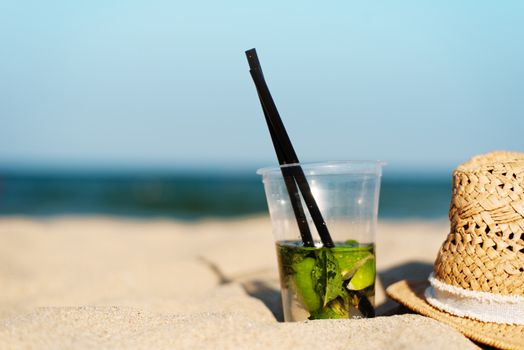 Mojito cocktail on the beach and straw hat. Blurred beach background with copy space. Sun, sun haze, glare