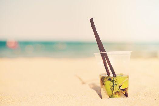 Mojito cocktail on the beach, blurred beach background. Sun, sun haze, glare