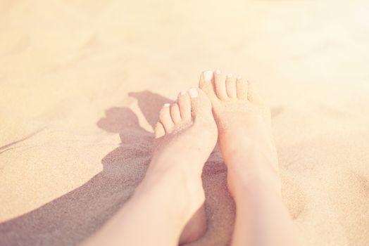 Holiday concept. Woman feet close-up relaxing on beach, enjoying sun and splendid view. Sandy feet on the beach. Sun, sun haze, glare