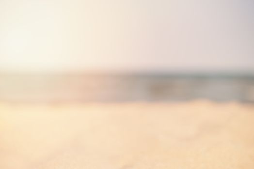 Blur summer white sand beach with sea water. Abstract bokeh blurred on colorful background. Space For Text. Sun, sun haze, glare