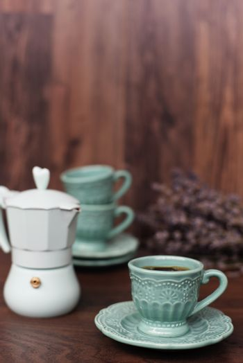 Cup of coffee and Italian coffee maker in blue, scent of lavender. Dark wooden background
