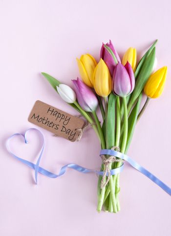 Heart shape ribbon attached to a bunch of flowers with mothers day label