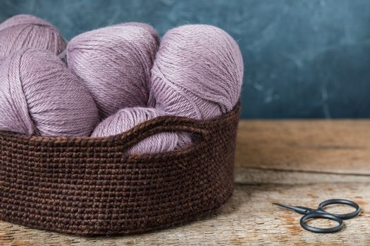 Pink wool yarn with scissors in the crocheted basket
