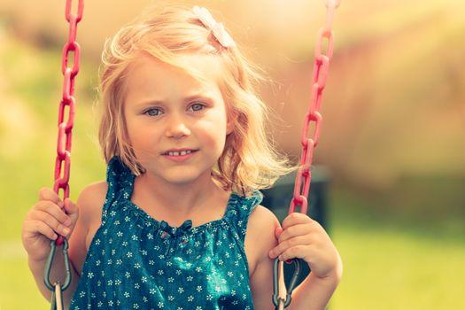 Cute baby girl swinging on swing