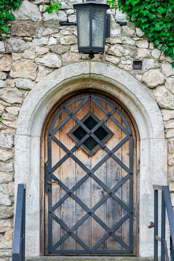 a wooden door with a metal grille in a medieval building, a lant
