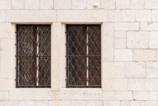 two window with a medieval-style grille in the castle