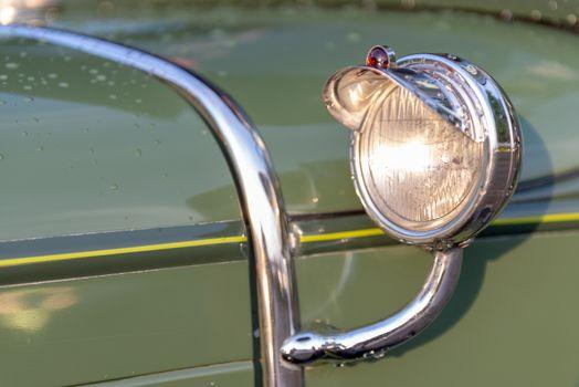 Headlamp and chrome detail on hood of vintage classic oldtimer car