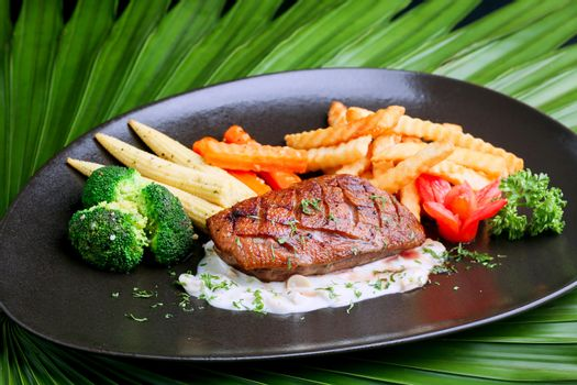Duck steak on black plate with potatoes and baby corn ,celery