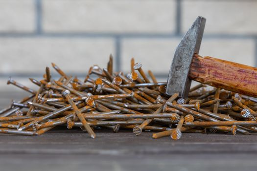 Rusty nails and an old hammer on the wooden background